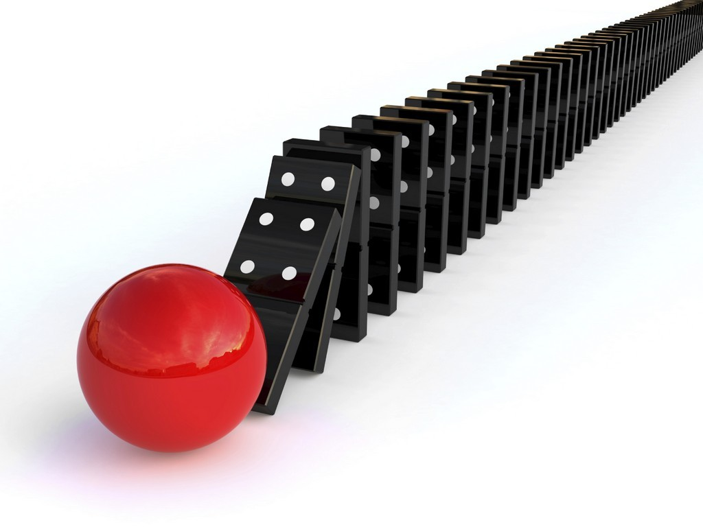 Line of dominoes knocked over by red ball, representing momentum for change