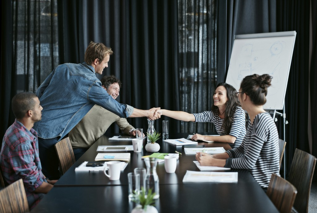 Friendly Handshake with Customer During Team Meeting