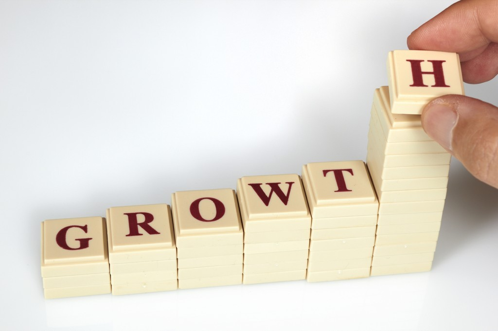 Letter Tiles Spelling GROWTH, Stacked in Shape of Business Growth Chart