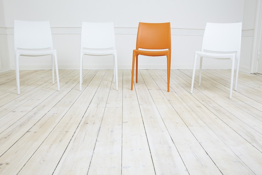 Unique Orange Chair Standing Out Amongst White Chairs